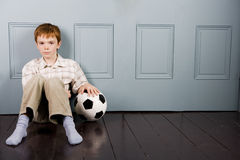 little boy sitting on floor with football Stock Images