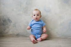 Little boy sitting on the floor near the wall Stock Photo
