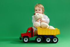 Little boy sitting on the floor and playing with toys, green background Stock Photography