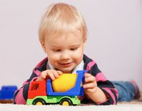 Little boy sitting on the floor and playing with toys, green background Stock Photos