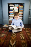 little boy sitting on the floor reading Royalty Free Stock Photo