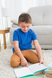 Little boy sitting on the floor reading storybook Stock Photo