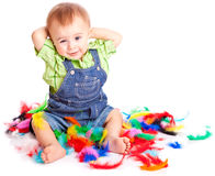 Little boy is sitting on a flow with feathers Stock Images