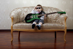 Little boy sitting on the glamorous couch Stock Images