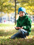 Little boy sitting on the grass in a cap and jacket and holding something. In his hands stock photography