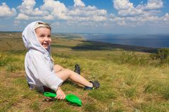 Little boy sitting on the grass and playing with shovel on the background of a picturesque landscape overlooking the sea. Royalty Free Stock Image
