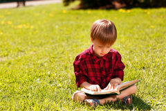 Little boy sitting on grass and reading book Royalty Free Stock Image