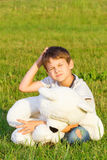 Little boy sitting on the grass with teddy bear and planning or thinking about something Stock Photography