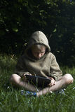 Little boy sitting on grass and using tablet computer. Little child boy sitting on green grass lawn outside and using tablet computer, summer time garden Royalty Free Stock Photo