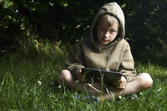 Little boy sitting on grass and using tablet computer. Little child boy sitting on green grass lawn outside and using tablet computer, summer time garden Stock Photo