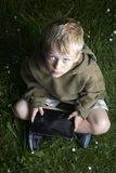 Little boy sitting on grass and using tablet computer. Little child boy sitting on green grass lawn outside and using tablet computer, summer time garden Royalty Free Stock Image