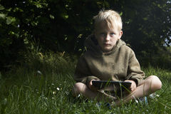 Little boy sitting on grass and using tablet computer. Little child boy sitting on green grass lawn outside and using tablet computer, summer time garden Royalty Free Stock Photography