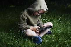 Little boy sitting on grass and using tablet computer Royalty Free Stock Images