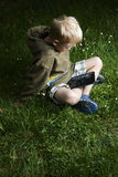 Little boy sitting on grass and using tablet computer Stock Photo