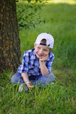 A little boy is sitting on the green grass in the park Royalty Free Stock Image