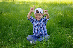 A little boy is sitting on the green grass in the park Royalty Free Stock Images