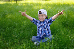 A little boy is sitting on the green grass in the park Royalty Free Stock Photo