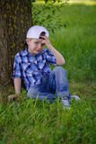 A little boy is sitting on the green grass in the park Royalty Free Stock Photography