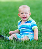 Little boy sitting in green lawn Stock Photos