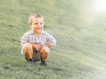 A little boy sitting on a green slope stock images