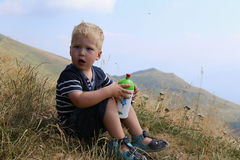 Little boy sitting on the hill side holding the drinking bottle Royalty Free Stock Image