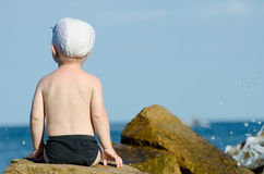 Little boy sitting with his back to a rock on the seashore in swimming trunks, blue sky. Space for text Royalty Free Stock Photography