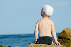 Little boy sitting with his back to a rock on the seashore in swimming trunks, blue sky Royalty Free Stock Photo
