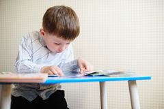 Little boy is sitting at his desk and reads a book Royalty Free Stock Images