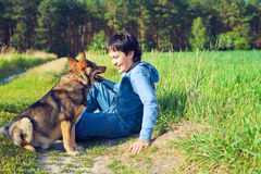 Little boy sitting with his dog. On the meadow Royalty Free Stock Image