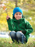 Little boy sitting on his haunches and waving a branch Royalty Free Stock Image