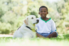 Little boy sitting with his pet labrador in the park Stock Image