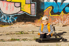 Little boy sitting with his scooter playing Royalty Free Stock Image