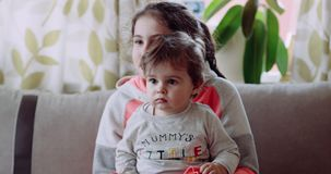 A little boy sitting in his sister`s arms ,and look at something, and she is smiling. 4k stock footage
