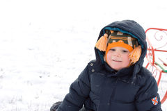 Little boy sitting with his sled in snow Stock Photo
