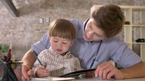 Little boy sitting with his young father at table and writing on paper, looking at tablet, modern office background.  stock video footage