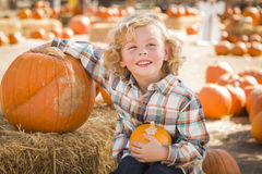 Little Boy Sitting and Holding His Pumpkin at Pumpkin Patch Stock Images