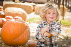 Little Boy Sitting and Holding His Pumpkin at Pumpkin Patch Royalty Free Stock Photography