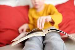 Little boy is sitting at home on the couch and reading a book. Learning to read stock photos