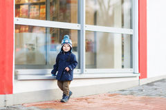 Little boy sitting infront of big window in the city, outdoors, Stock Images