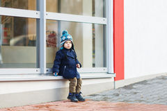 Little boy sitting infront of big window in the city, outdoors, Royalty Free Stock Images