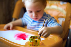 A little boy is sitting at the kids table, holding a brush, paint, paints stock photos