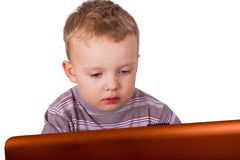 Little boy sitting at a laptop Stock Image