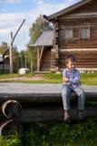 Boy is sitting on logs in village. Little boy is sitting on logs Stock Photography