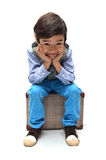 Little boy sitting on luggage Stock Photo