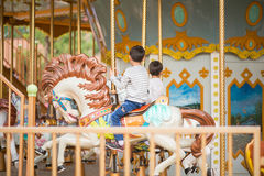 Little boy sitting in marry go round in amusement park. Outdoor Royalty Free Stock Photos
