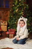 Little boy sitting near a Christmas tree Stock Photo