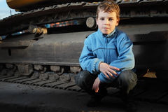 Little boy sitting near crawler tractor Stock Photos