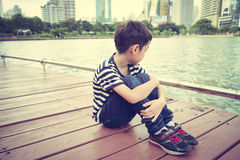 Little boy sitting nearby the lagoon in the pard alone Stock Images