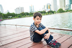 Little boy sitting nearby the lagoon in the pard alone Royalty Free Stock Image