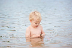 A little boy sitting in the ocean Royalty Free Stock Images